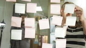 创造性的女实业家和人激发灵感会议的在现代玻璃办公室 使用不同的颜色贴纸 股票视频