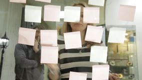 创造性的女实业家和人激发灵感会议的在现代玻璃办公室 使用不同的颜色贴纸 影视素材