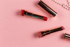 创造性的女性化妆用品平的位置唇膏的在与拷贝空间的五颜六色的桃红色背景 免版税库存照片