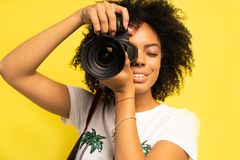 创造性的妇女摄影师拍照片,隔绝在黄色 免版税库存图片
