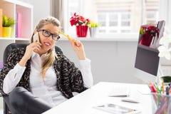 创造性的妇女谈话在电话,当坐在书桌在办公室时 免版税库存照片