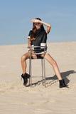创造性的射击在沙漠 一件黑礼服的一个美丽的性感的女孩 T 免版税库存照片