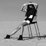 创造性的射击在沙漠 一件黑礼服的一个美丽的性感的女孩 T 库存图片