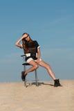 创造性的射击在沙漠 一件黑礼服的一个美丽的性感的女孩 T 库存照片