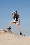创造性的射击在沙漠 一件黑礼服的一个美丽的性感的女孩 T 免版税库存图片