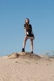 创造性的射击在沙漠 一件黑礼服的一个美丽的性感的女孩 T 图库摄影