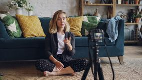 创造性的少妇记录她的订户的录影互联网videolog的,她看在三脚架的照相机 影视素材