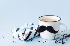 创造性的早餐在与礼物盒和滑稽的面孔的愉快的父亲节从咖啡和髭 库存照片