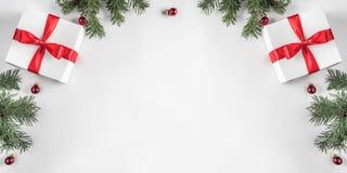创造性的框架由圣诞节冷杉分支做成在与红色装饰,杉木锥体的白皮书背景 免版税库存图片