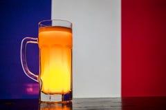 创造性的概念 品脱在桌上的新鲜的啤酒与法国的被弄脏的旗子背景或杯的储藏啤酒准备好饮料 Co 免版税图库摄影