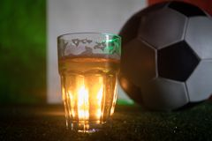 创造性的概念 品脱在草的新鲜的啤酒与意大利的被弄脏的旗子背景或杯的储藏啤酒准备好饮料 警察 免版税库存照片