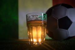 创造性的概念 品脱在草的新鲜的啤酒与意大利的被弄脏的旗子背景或杯的储藏啤酒准备好饮料 警察 库存照片