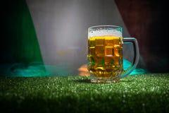 创造性的概念 品脱在草的新鲜的啤酒与意大利的被弄脏的旗子背景或杯的储藏啤酒准备好饮料 警察 图库摄影