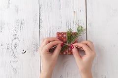 创造性的爱好 妇女` s手包裹在工艺纸的圣诞节假日手工制造礼物与麻线丝带 做在xmas礼物b的弓 免版税库存照片