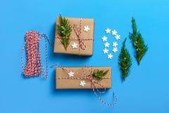 创造性的爱好 礼品包装材料 在时髦的灰色纸的包装的现代圣诞节礼物箱子与缎红色丝带 免版税库存照片