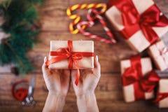 创造性的爱好 Woman& x27; s手在与丝带的工艺纸显示圣诞节假日手工制造礼物 做在xmas的弓 免版税库存照片