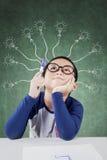 创造性的男小学生举行笔和想法的想法 免版税库存照片