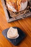 创造性的美好的Dinning :在秸杆的新鲜的被烘烤的面包在木箱服务用自创黄油 库存图片