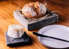创造性的美好的Dinning :在秸杆的新鲜的被烘烤的面包在木箱服务用自创黄油 库存照片
