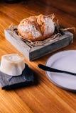 创造性的美好的Dinning :在秸杆的新鲜的被烘烤的面包在木箱服务用自创黄油 免版税库存照片