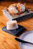 创造性的美好的Dinning :在秸杆的新鲜的被烘烤的面包在木箱服务用自创黄油 免版税库存图片