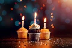 创造性的背景,与蜡烛的杯形蛋糕,美好的bokeh E ?? 假日卡片的,飞行物概念 免版税图库摄影
