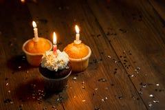 创造性的背景,与蜡烛的杯形蛋糕,美好的bokeh E ?? 假日卡片的,飞行物概念 免版税库存图片