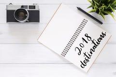 创造性的舱内甲板在木背景放置工作区书桌和笔照片有2018年目的地新年名单笔记本的 库存照片
