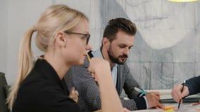 创造性的见面在起始的办公室的小企业队年轻建筑师有效地谈论新的想法 股票录像