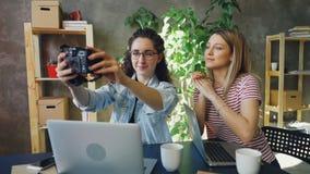 创造性的设计师为一起坐在现代办公室的selfie摆在 他们使用照相机,笑和 股票录像
