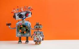 创造性的设计机器人家庭 大机器人电线发型,插座胳膊 有电灯泡玩具的小孩子靠机械装置维持生命的人 复制 免版税图库摄影
