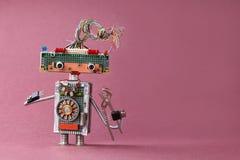 创造性的设计玩具电工钳子在手中 有电导线发型的,电子线路,芯片五颜六色的机器人 图库摄影