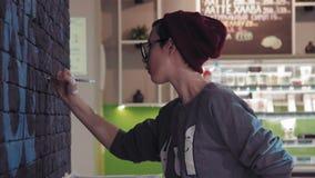 创造性的转移在黑砖墙上的画家年轻女性艺术家图形设计在咖啡店使用 影视素材