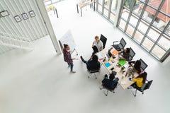 创造性的队小组的不同的人顶视图使用智能手机、手机、片剂和计算机膝上型计算机的,当见面时 库存图片