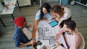 创造性的队谈论项目在看纸的工作然后举胳膊 股票视频