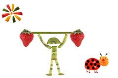 创造性的食物概念 有切片的滑稽的小男孩猕猴桃 免版税库存图片