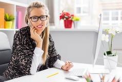 创造性的年轻女商人谈话在电话在办公室 免版税库存图片