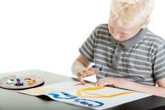 创造性的年轻男孩手指画法在家 库存图片