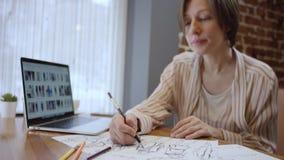 创造性的fashio设计师接近的射击便服的,看在膝上型计算机和画的剪影上 二妇女 影视素材
