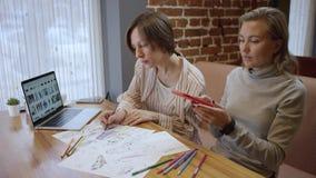 创造性的fashio设计师接近的射击便服的,看在膝上型计算机和画的剪影上 二妇女 股票录像