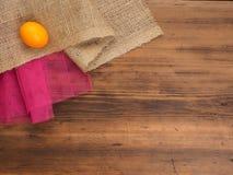 创造性,土气背景 橙色鸡鸡蛋、粗麻布和一个红色栅格的构成在棕色背景从老 免版税库存照片