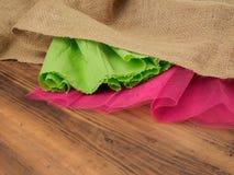 创造性,土气背景 粗麻布、卷曲的绿皮书和一个红色栅格的构成在棕色背景从 库存照片
