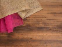 创造性,土气背景 粗麻布的构成和在棕色背景的一个红色栅格从老木头,农村桌 库存照片
