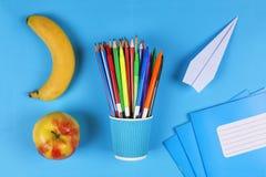 创造性, minimalistic样式 回到概念学校 教育快餐,学校,办公用品,香蕉,苹果,与拷贝温泉的平的位置 库存图片