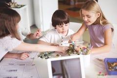 创造机器人的快乐的孩子在教训期间 免版税库存照片