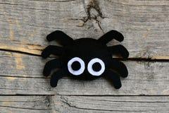 创造毛毡万圣夜蜘蛛装饰品 步骤 在葡萄酒木背景隔绝的逗人喜爱的万圣夜蜘蛛装饰品 库存照片