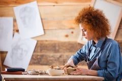创造盘的严肃的妇女陶瓷工用黏土用人工 免版税库存照片