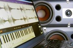 创造音乐在膝上型计算机的一位编辑,被弄脏的背景报告人 免版税库存图片