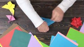 创造origami用蓝纸,顶视图的男性手 股票视频