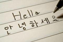 初学者写你好词的韩语学习者在韩国字符宏观射击 图库摄影